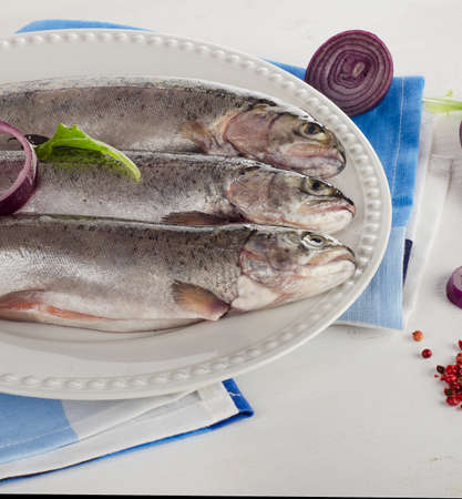 salmon fishery: Rainbow trouts on  white plate with herbs.