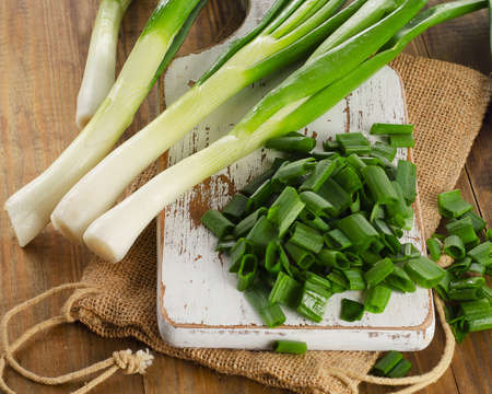 Green onion on a   wooden cutting board. Selective focus
