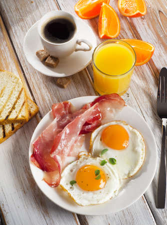 Eggs, bacon, orange juice and coffee for healthy breakfast.