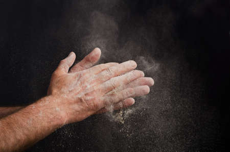haciendo pan: Chef mano con harina en el fondo negro