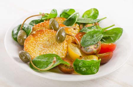 alcaparras: Rebanadas de queso halloumi con alcaparras y verduras. Enfoque selectivo