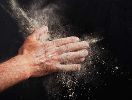 haciendo pan: Cocinero de la mano con una harina sobre fondo negro