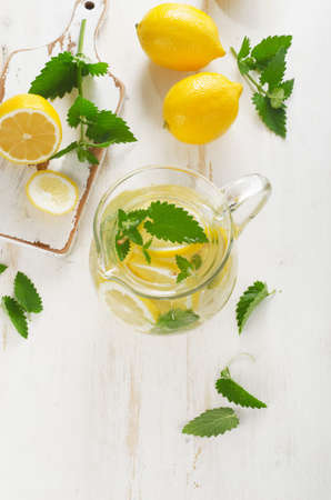 lemon water: Cold Water with fresh lemon and mint in a glass jug. Top view
