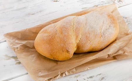 ciabatta: Italian bread ciabatta on wooden table. Selective focus