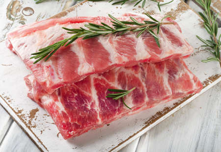 pork meat: Raw ribs with a rosemary on a white wooden table