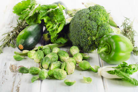 Frische grüne Gemüse auf einem weißen Holztisch. Selektiver Fokus