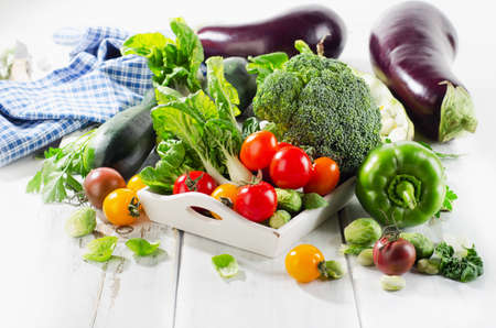 Fresh green organic vegetables on white wooden background. Selective focus 스톡 콘텐츠