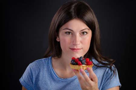 sweet tart: Young smiling woman eating sweet tart with fresh berries. Stock Photo