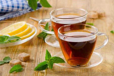 나무 테이블에 민트와 레몬 차의 유리 컵. 선택적 포커스