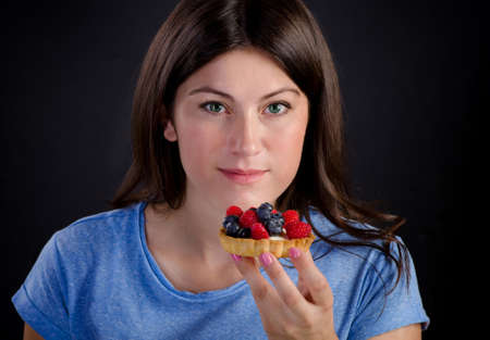 sweet tart: Young smiling woman eating sweet tart with fresh berries. Stock Photo