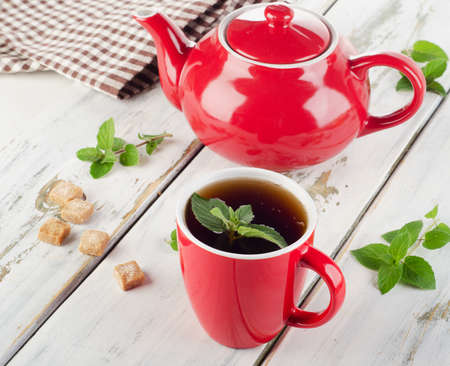 red green: Teapot and cup with fresh mint on  wooden table. Selective focus Stock Photo