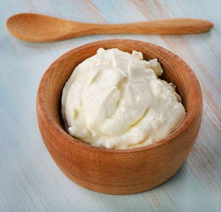 yogurt: Fresh yogurt in wooden bowl. Selective focus Stock Photo