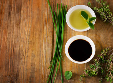olive: Olive oil, balsamic vinegar and herbs on a vintage wooden background from above.