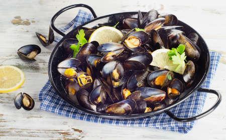 lemon slices: Copper pot of mussels garnished with lemon slices. Selective focus