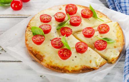 margherita: Italian Pizza Margherita on a wooden table.