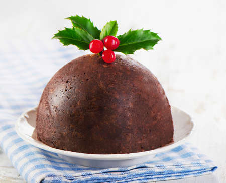 Christmas plum pudding with holly. Selective focus Stock Photo