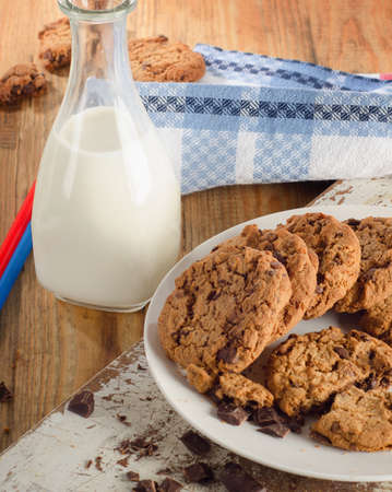 bootle: Chocolate chip cookies with bootle of milk on a wooden background. Top view Stock Photo