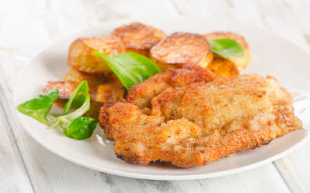 schnitzel: Homemade Breaded Schnitzel with Potatoes and Salad. Selective Focus