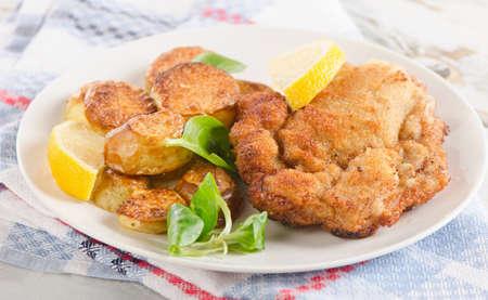 schnitzel: Homemade Breaded Schnitzel with Potatoes and Lemon. Selective Focus