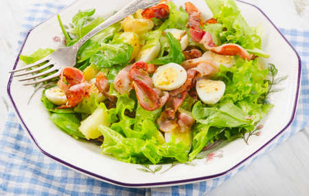 bacon and eggs: Warm salad with bacon, eggs and potatoes. Top view