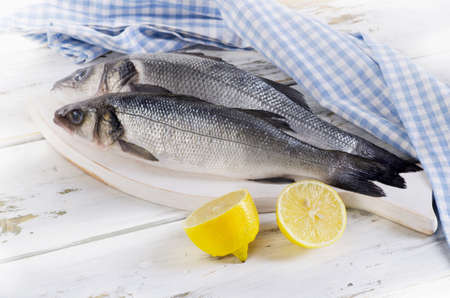 Two raw seabass with lemon on wooden background.