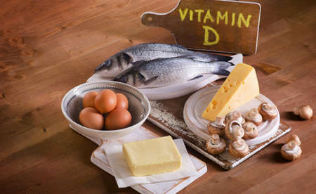 d: Foods containing vitamin D on a wooden background.