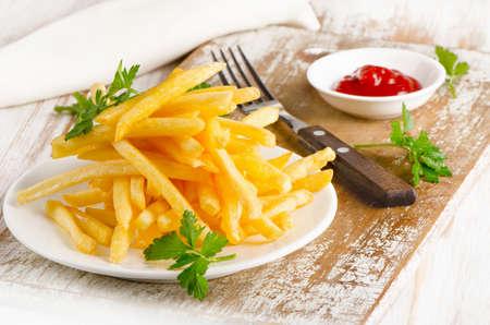 papas fritas: patatas fritas en una tabla de madera. enfoque selectivo Foto de archivo