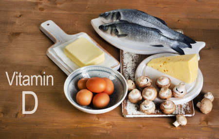 Foods containing vitamin D on a wooden table. View from above