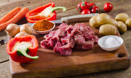 stewing: Ingredients for goulash  on a rustic wooden table. Top view