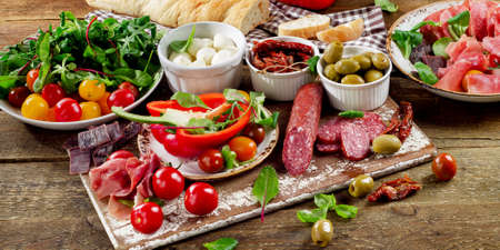 comida italiana: Aperitivos en una tabla de cortar de madera.