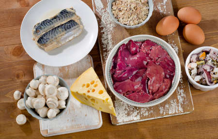 vitamina a: Los alimentos más ricos en vitamina B12 (cobalamina) sobre un fondo de madera. Alimentación saludable. Vista desde arriba