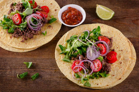 two on top: Two mexican tacos on wooden table. Top view
