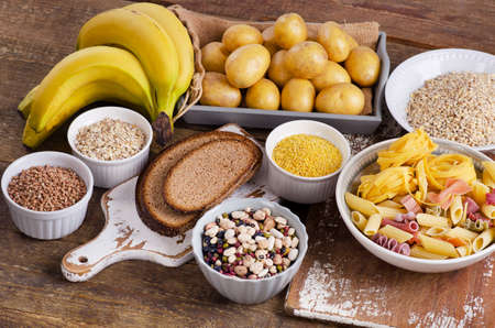 Foods high in carbohydrate on wooden table. Top view Archivio Fotografico