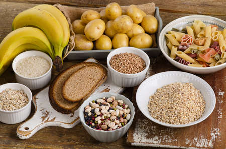 Foods high in carbohydrate on a wooden background. Top view Stock Photo