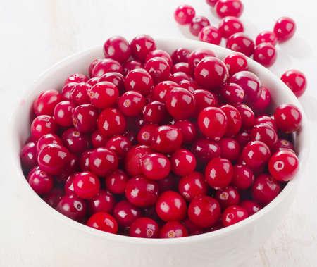 arandanos rojos: Fresh cranberries in white bowl.