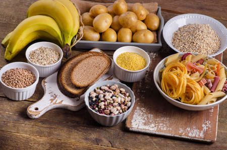 Foods high in carbohydrate on rustic wooden background. Top view Stockfoto