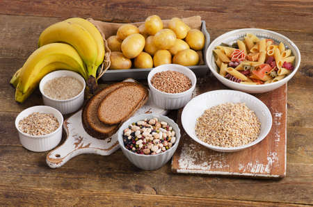 Foods high in carbohydrate on wooden background. Top view Standard-Bild