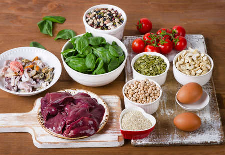 Foods high in Iron, including eggs, nuts, spinach, beans, seafood, liver, sesame, tomatoes. Top view