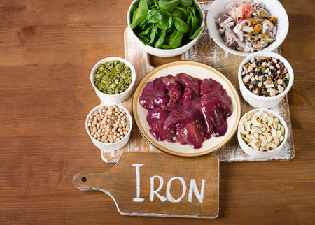 Foods high in Iron on wooden board. Top view