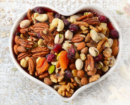 apricot kernels: Nuts on heart plate. Healthy diet eating. Top view Stock Photo