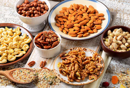 apricot kernels: Assorted mixed nuts on wooden table.
