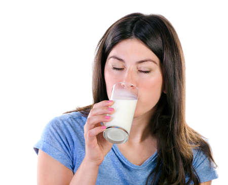 woman drinking milk: Young woman drinking milk over  white background. Stock Photo