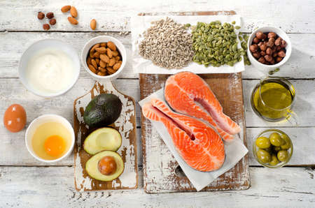 unsaturated: Healthy Food: Best Sources of unsaturated fats on a white wooden background. Top view Stock Photo
