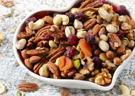 apricot kernels: Nuts on heart plate. Healthy  eating concept. Stock Photo