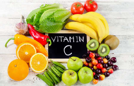 Foods High in vitamin C on a wooden board.  Healthy eating. Flat lay 免版税图像