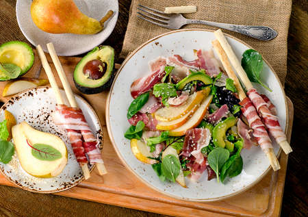 gressins: Fresh mixed salad with pancetta and breadsticks on  wooden table. Flat lay