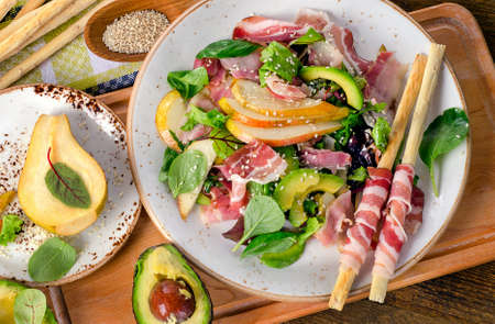 gressins: Fresh mixed salad with pancetta and breadsticks on a rustic wooden table. Top view Banque d'images
