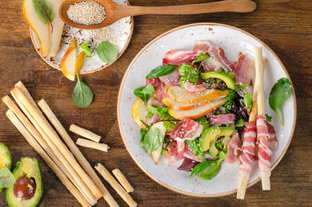 gressins: Fresh mixed salad with pancetta and breadsticks on a rustic wooden table. Flat lay
