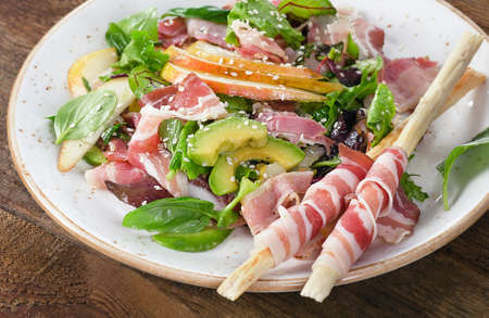 gressins: Fresh mixed salad with pancetta and breadsticks on a wooden table.