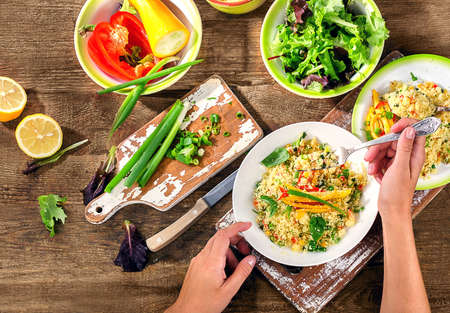 plates of food: Woman Hands holding plate of Couscous with vegetables.  Flat lay Stock Photo